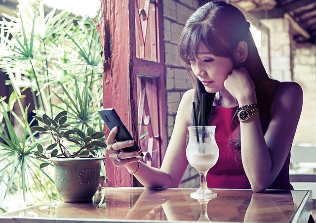Chica triste mira el móvil